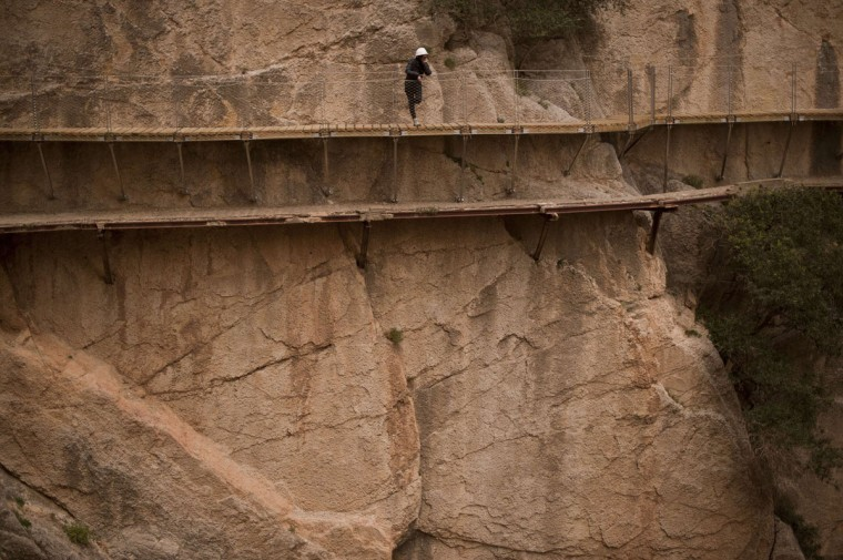 "A person admires the scenery during a visit to the foot-path ""El Caminito del Rey"" (King's little path) a narrow walkway hanging and carved on the steep walls of a defile in Ardales near Malaga on March 15, 2015. (Jorge Guerrero/AFP/Getty Images)"