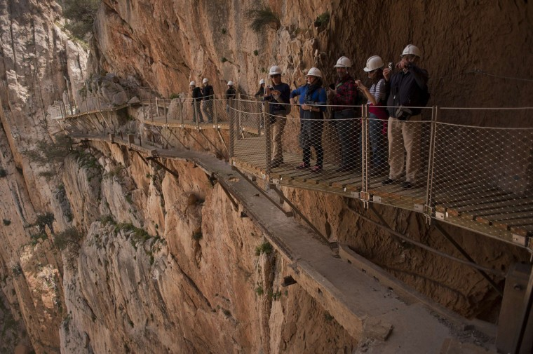 "Journalists and visitors take photographs during a visit to the foot-path ""El Caminito del Rey"" (King's little path), a narrow walkway hanging and carved on the steep walls of a defile in Ardales near Malaga on March 15, 2015. (Jorge Guerrero/AFP/Getty Images)"
