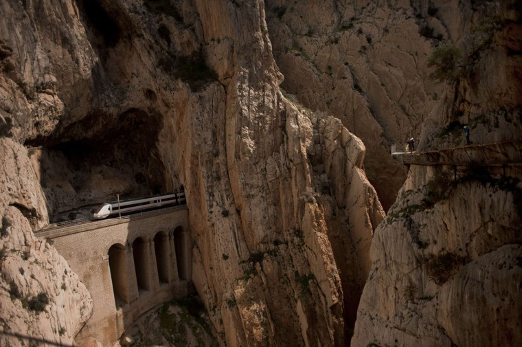 "A train passes through a tunnel in the rocks as people walk the foot-path ""El Caminito del Rey."" (Jorge Guerrero/AFP/Getty Images)"