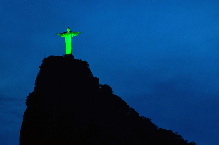 View of the statue of Christ the Redeemer illuminated in green to celebrate the upcoming Irish festivity of Saint Patrick's Day, atop Corcovado hill in Rio de Janeiro, Brazil, on March 15, 2015. (AFP Photo/Yasuyoshi Chiba)