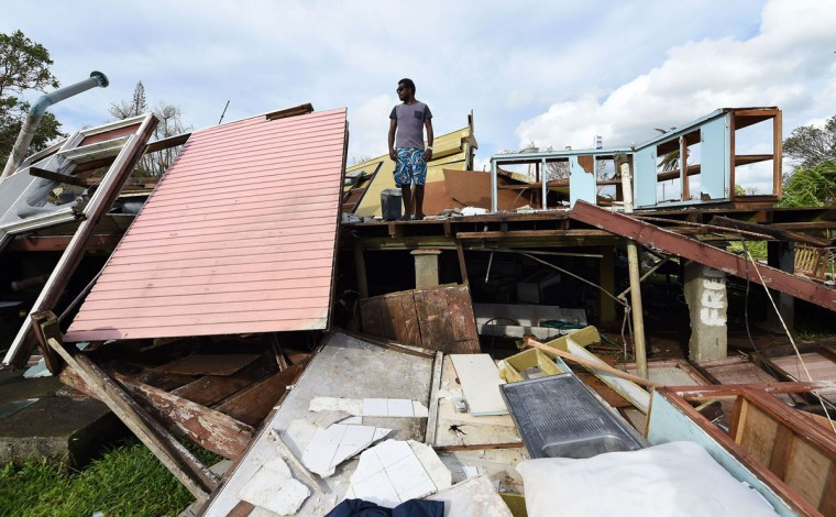 Adrian Banga surveys his house, flattened by Cyclone Pam, in Vanuatu's capital Port Vila on March 16, 2015. Vanuatu's president on March 16 pleaded with the world to help the cyclone-ravaged Pacific nation rebuild as aid agencies warned conditions were among the most challenging they have ever faced with fears of disease rife. (AFP Photo/Dave Hunt)