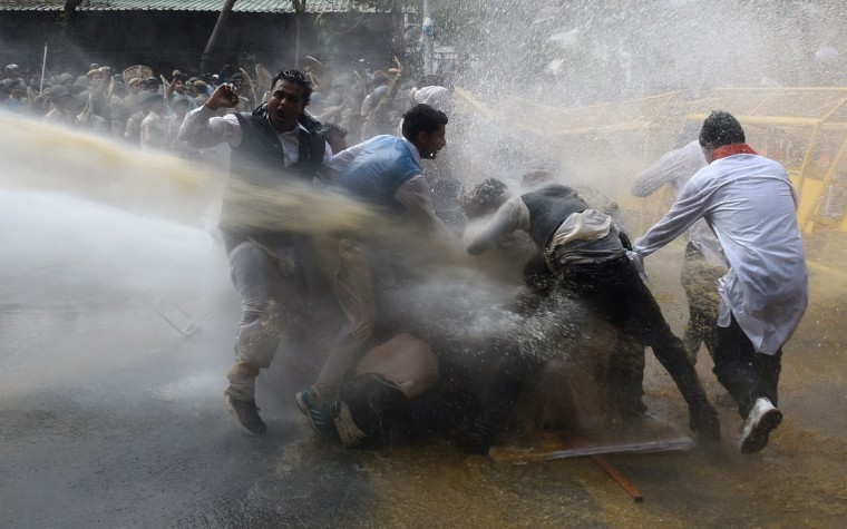 Police use water cannon to disperse protesters led by the opposition Congress party in New Delhi on March 16, 2015. Police on March 16 baton-charged and fired water cannon at demonstrators rallying in the Indian capital against Prime Minister Narendra Modi's land reforms, which they say will harm the country's millions of farmers. (AFP Photo/Money Sharma)