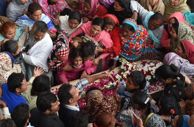 Pakistani Christians mourn over the coffin of the victim of a suicide bomb attack on a church in Lahore on March 16, 2015. Thousands of Christians rioted in the Pakistani city of Lahore, smashing property and vehicles as they clashed with police in a second day of protest against twin Taliban suicide bombings of churches that killed 17 people. (AFP Photo/Arif Ali)