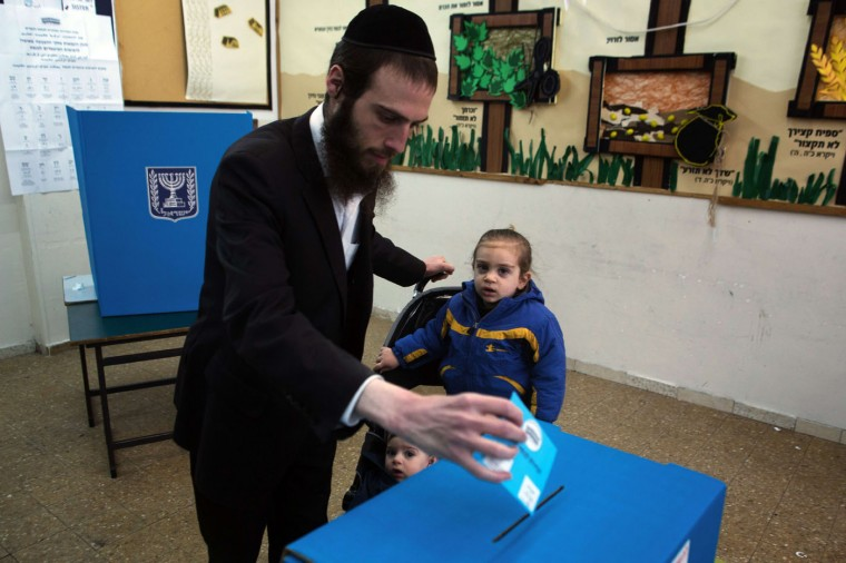 An Israeli ultra-orthodox Jewish man casts his ballot with his children at a polling station in Jerusalem on March 17, 2015. Israelis are voting in a close-fought election pitting the centre left against Prime Minister Benjamin Netanyahu, who ruled out a Palestinian state in a last-ditch appeal to the far-right. (Menahem Kahana/AFP/Getty Images)