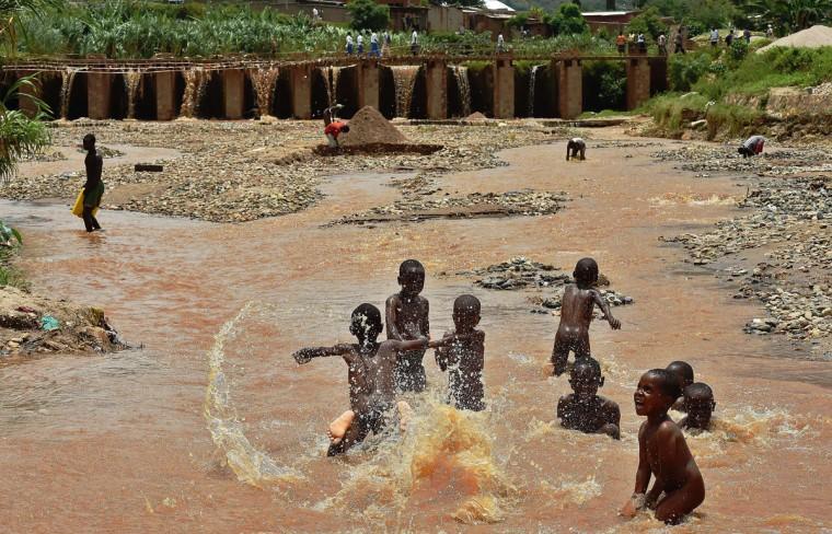 Children play in water in Bujumbura, on March 19, 2015. (AFP Photo/Carl Souzacarl de souza)