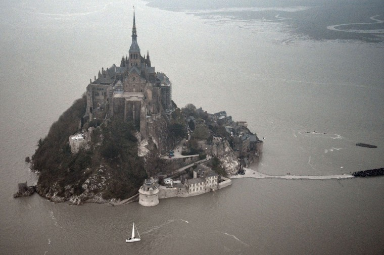 """An aerial view of Mont-Saint-Michel surrounded by the sea during high tide on March 20, 2015. A """"supertide"""" is expected on March 21 that will affect coastlines around the North Sea, the English Channel and to a lesser extent in the Mediterranean. The world-famous Mont Saint-Michel on France's northern coast is braced for an especially big tide, with a difference between high and low tide of 14.15 meters. (Damien Meyer/AFP-Getty Images)"""