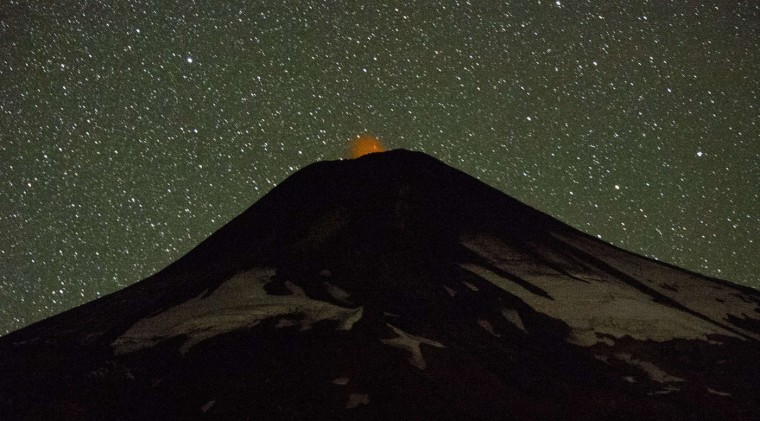 View of the Villarrica volcano from Pucon, some 800 km south of Santiago, showing visible signs of activity on March 20, 2015. Earlier this month, in its first major eruption in 15 years, the Villarrica forced the evacuation of thousands of people amid a shower of fire and ash. (Martin Bernetti/AFP/Getty Images)