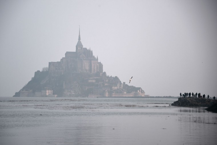 """Mont-Saint-Michel is surrounded by the sea during high tide on March 20, 2015. A """"supertide"""" is expected on March 21 that will affect coastlines around the North Sea, the English Channel and to a lesser extent in the Mediterranean. The world-famous Mont Saint-Michel on France's northern coast is braced for an especially big tide, with a difference between high and low tide of 14.15 meters. (Damien Meyer/AFP-Getty Images)"""