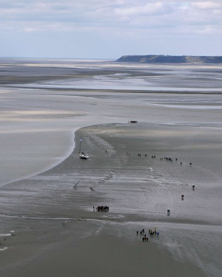 """People walk at low tide around Mont-Saint-Michel as thousands flocked to there to watch what they hoped would be a """"tide of the century"""" surround the picturesque landmark on France's northern coast. (Guillaume Souvant/AFP-Getty Images)"""