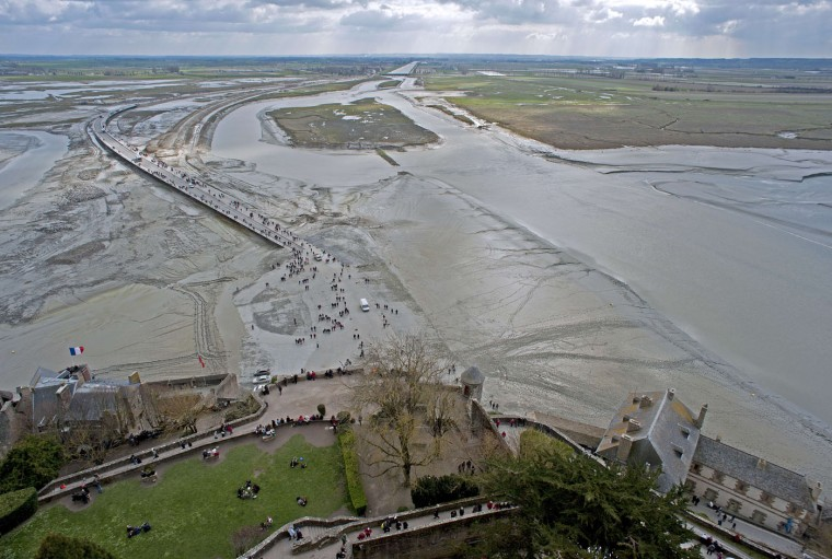 """People wait for the wave named """"Mascaret"""" in front of the Mont-Saint-Michel. Thousands of people flocked to Mont Saint-Michel, a Gothic Benedictine abbey perched on a rocky island, to watch what they hoped would be a """"tide of the century"""" surround the picturesque landmark on France's northern coast. (Guillaume Souvant/AFP-Getty Images)"""