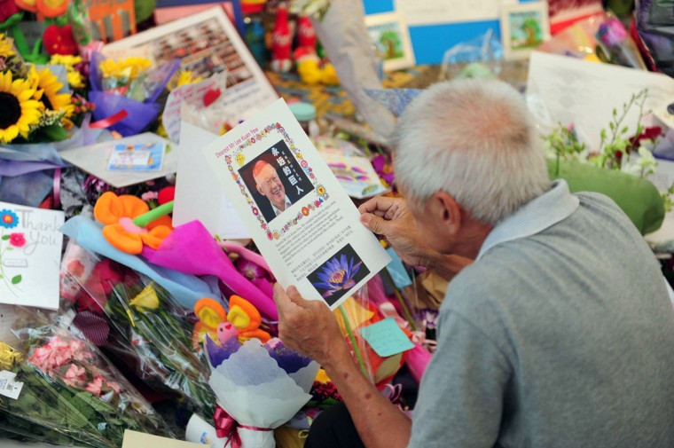 A man reads a card left at the tribute area at Singapore General Hospital following the death of former prime minister Lee Kuan Yew in Singapore on March 23, 2015. Singapore's first prime minister Lee Kuan Yew, one of the towering figures of post-colonial Asian politics, died at the age of 91 on March 23 in hospital, the government said. (AFP Photo/Mohd Fyrol)