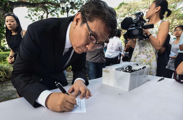 Thailand's ambassador-designate to Singapore, Bansarn Bunnag writes a message of condolence before posting it on a board outside the Istana presidential palace in honour of Singapore's former prime minister Lee Kuan Yew in Singapore on March 23, 2015. Singapore's first prime minister Lee Kuan Yew, one of the towering figures of post-colonial Asian politics, died at the age of 91 on March 23 in hospital, the government said. (AFP Photo/Stefanus Ian)