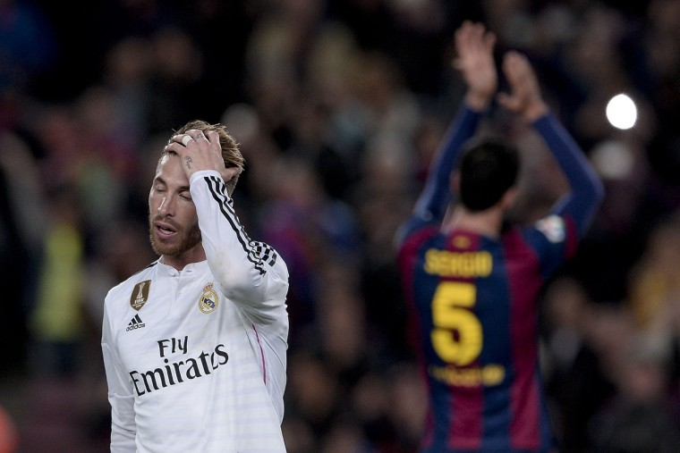 "Real Madrid's defender Sergio Ramos (L) touches his head as Barcelona's midfielder Sergio Busquets claps during the ""clasico"" Spanish league football match FC Barcelona vs Real Madrid CF at the Camp Nou stadium in Barcelona on March 22, 2015. (AFP Photo/Josep Lago)"