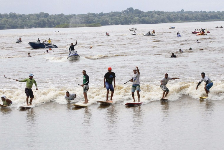 "People surf on the wave of a tidal bore known as ""Pororoca"" during the annual surfing Pororoca festival in Sao Domingos do Capim. (LUCIVALDO SENA/AFP/Getty Images)"