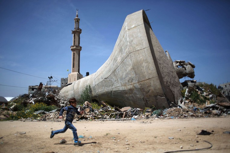 A Palestinian child runs past a water tank that was destroyed in Israeli bombing during the 50-day war between Israel and Hamas militants in the summer of 2014, in the village of Khuzaa, east of Khan Yunis, in the southern Gaza Strip on March 26, 2015. (AFP Photo/Said Khatib)