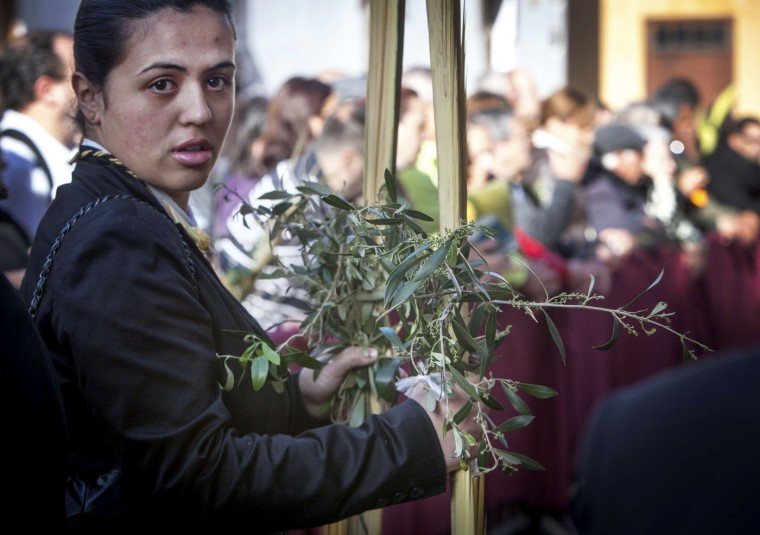 A woman takes holds palm and olive branches blessed during the morning Mass at the Cathedral of San Cristobal de La Laguna during a procession commemorating the arrival of Jesus in Jerusalem, on the Spanish Canary island of Tenerife on March 29, 2015. Palm Sunday held annually on the Sunday before Easter and commemorates the entry into Jerusalem of Jesus Christ. (Desiree Martin/AFP/Getty Images)