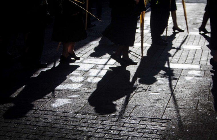 Shadows are cast on the street as people holding palm and olive branches blessed during the morning Mass at the Cathedral of San Cristobal de La Laguna walk during a procession commemorating the arrival of Jesus in Jerusalem, on the Spanish Canary island of Tenerife on March 29, 2015. Palm Sunday held annually on the Sunday before Easter and commemorates the entry into Jerusalem of Jesus Christ. (Desiree Martin/AFP/Getty Images)