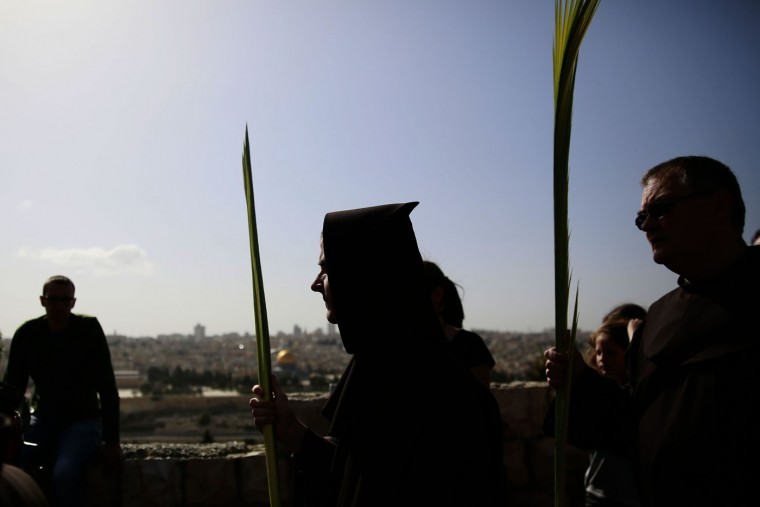 Franciscan friar carry palm branch during the traditional Palm Sunday procession from Mt. Olives to Jerusalem's Old City on May 29, 2015. The ceremony is a landmark in the Christian calendar, marking the triumphant return of Christ to Jerusalem the week before his death, when a cheering crowd greeted him waving palm leaves. Palm Sunday marks the start of the most solemn week in the Christian calendar. (Gali Tibbon/AFP/Getty Images)