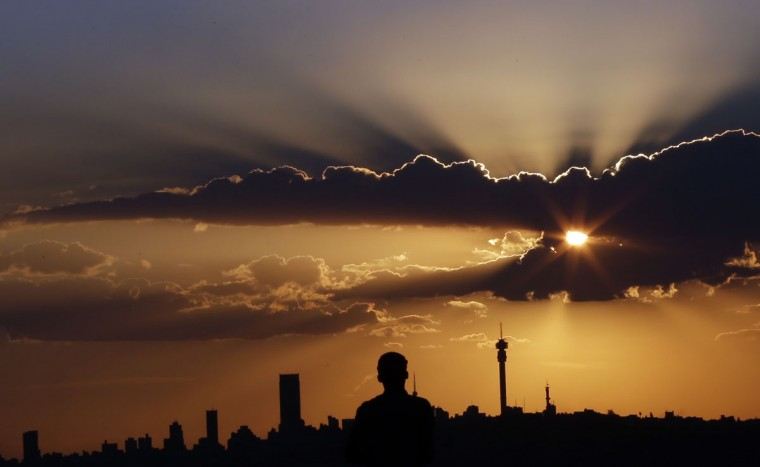 A man watches the sun set in as he overlooks the skyline in Johannesburg, South Africa, Tuesday, March. 10, 2015. (AP Photo/Themba Hadebe)