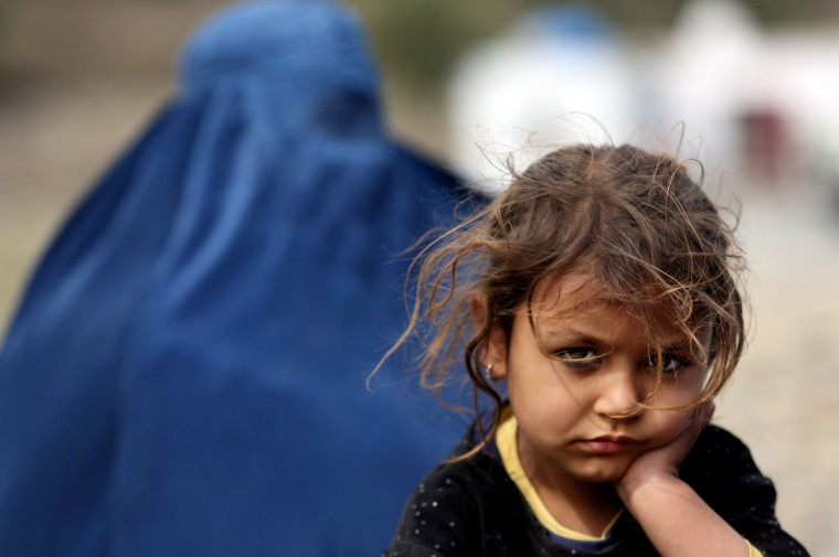 In Wednesday, March 11, 2015 photo, an Afghan refugee girl who arrived to Afghanistan through Pakistan's border crossing, poses for a photograph at the International Organization for Migration center, in Torkham, east of Kabul, Afghanistan. Since January, almost 50,000 Afghan families have passed through Torkham, double the amount of all refugees returning through the border town in 2014, according to the International Organization for Migration. Many say they fled Pakistan over increased harassment by police who told them to return to Afghanistan, a country many have never even seen, putting new pressure on both countries to find solutions to the decades-old flow of refugees. (AP Photo/Rahmat Gul)