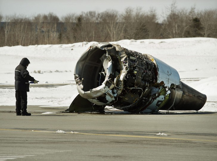 A Transportation Safety Board investigator inspects an engine, Monday, March 30, 2015, at the crash site of Air Canada AC624 that crashed early Sunday during a snowstorm, at Stanfield International Airport in Halifax, Nova Scotia. The Air Canada passenger plane landed so significantly short of the runway in Halifax that it hit a power line and knocked out power at the airport, the lead investigator said Monday. (AP Photo/The Canadian Press, Andrew Vaughan)