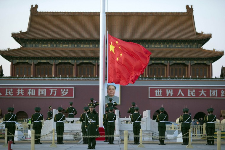 Chinese paramilitary policemen perform a flag-lowering ceremony near a portrait of Mao Zedong on Tiananmen Gate in Beijing, Monday, March 9, 2015. Thousands of delegates from across the country are in the Chinese capital this week to attend the Chinese People's Political Consultative Conference and the National People's Congress. (AP Photo/Ng Han Guan)