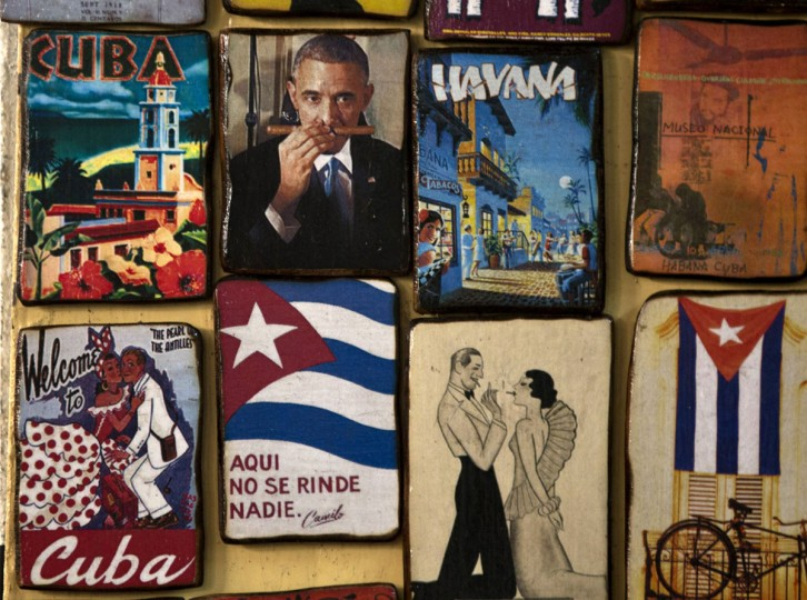 "Magnets for sale decorate a tourist shop, one showing an image of U.S. President Barack Obama smelling a cigar, at a market in Havana, Cuba, Monday, March 16, 2015. U.S. and Cuban officials are meeting Monday in last-minute closed door negotiations in Havana, in hopes of restoring full diplomatic relations before the Summit of the Americas in April. The magnet in the bottom row, second from left, reads in Spanish: ""Here, nobody gives up,"" a popular quote attributed to Cuba's late revolutionary hero Camilo Cienfuegos. (AP Photo/Ramon Espinosa)"