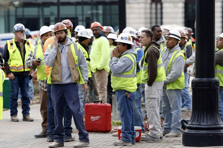 Construction workers gather outside the scene where a section of scaffolding collapsed at a high-rise construction project, killing three people and sending another to a hospital, Monday, March 23, 2015, in downtown Raleigh, N.C. (AP Photo/The News & Observer, Harry Lynch)