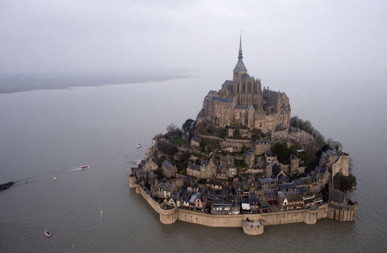 """An aerial view as a high tide submerges a narrow causeway leading to the Mont Saint-Michel, on France's northern coast. A supertide has turned France's famed Mont Saint-Michel into an island and then retreated out of sight, delighting thousands of visitors who came to see the rare phenomenon. The so-called """"tide of the century"""" actually happens every 18 years. (Associated Press)"""