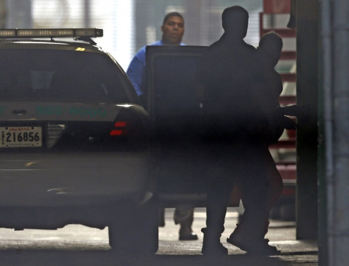 Robert Durst, far right, photographed through fencing, is escorted into Orleans Parish Criminal District Court through a tunnel entrance, in New Orleans, Monday, March 16, 2015. Durst waived extradition Monday and will return to Los Angeles to face a murder charge in the 15-year-old death of a writer and friend who acted as his spokeswoman. (AP Photo/Gerald Herbert)