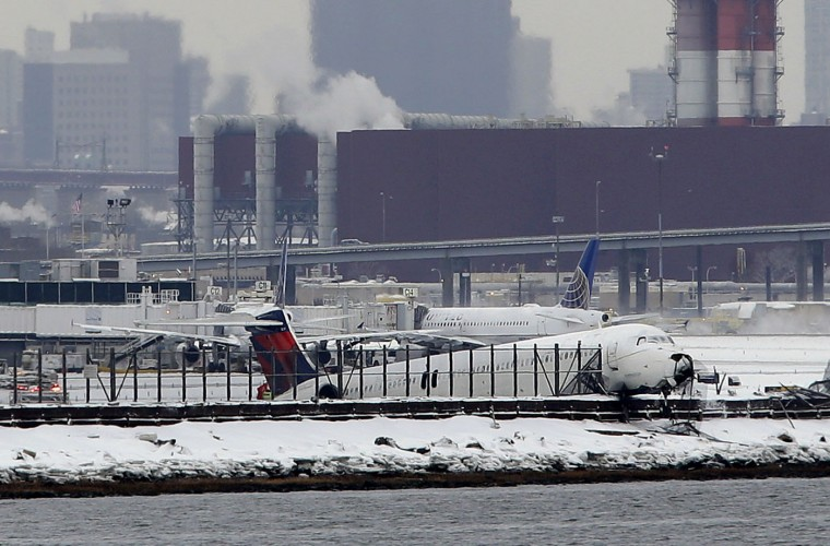 A plane that skidded off the runway at LaGuardia Airport hangs over the edge of the runway in New York, Thursday, March 5, 2015. The plane, from Atlanta, skidded off the runway while landing, and crashed through a chain-link fence. (AP Photo/Seth Wenig)