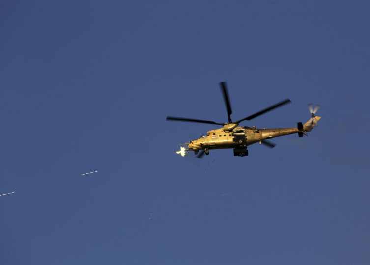 An Iraqi military helicopter attacks Islamic State group positions during clashes in Tikrit, 130 kilometers (80 miles) north of Baghdad, Iraq, Thursday, March 26, 2015. Iraqi troops started the final phase of an offensive to recapture Saddam Hussein's hometown of Tikrit on Thursday, a military official said, just hours after the United States launched airstrikes on the Islamic State held city. (AP Photo/Khalid Mohammed)