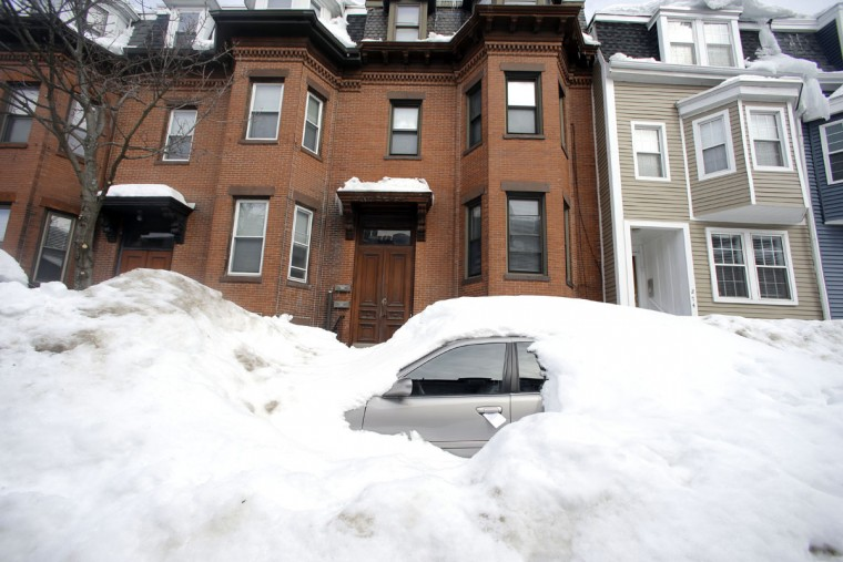 In this Feb. 23, 2015 photo, a car remains buried in snow along a residential street in South Boston. Officials typically turn a blind eye to the lawn chairs, orange cones and assorted bric-a-brac Bostonians use to reserve a parking space after clearing it of snow. That ends Monday, March 2, 2015, with an order from City Hall to remove space savers, reigniting the ugly parking wars that have pitted neighbor against neighbor. (AP Photo/Elise Amendola)
