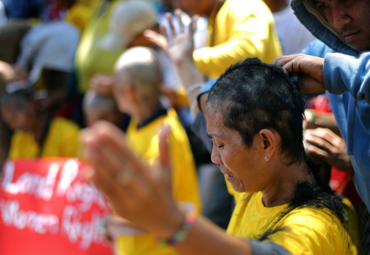 A Filipino woman has her head shaved during a rally at the gates of the House of Representatives in suburban Quezon city, north of Manila, Philippines on Monday March 9, 2015. Fifteen women farmers had their heads shaved to protest the alleged failure of the House of Representatives to immediately pass bills that could extend and overhaul the implementation of the Comprehensive Agrarian Reform Program (CARP). (AP Photo/Aaron Favila)