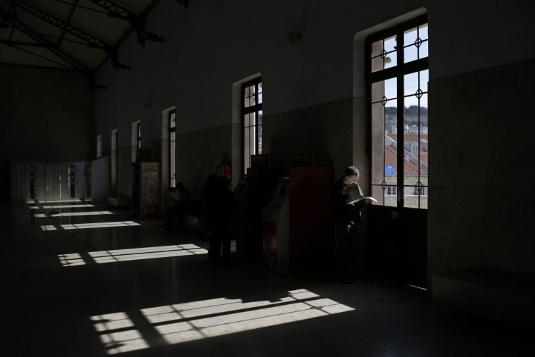 A man reads a newspaper by a window at the Rossio train station in Lisbon, Portugal, Thursday, March 5, 2015. The station located in the city centre is frequented by local commuters from outside the Portuguese capital and tourists who want to visit the historical town of Sintra. (AP Photo/Francisco Seco)