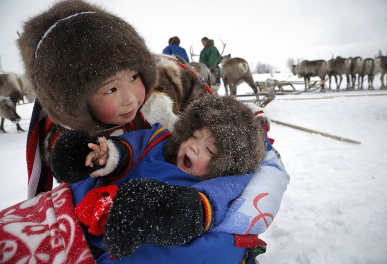 In this photo taken on Sunday, March 15, 2015, Nenets children attend the Reindeer Herder's Day holiday in the city of Nadym, in Yamal-Nenets Region, 2500 kilometers (about 1553 miles) northeast of Moscow, Russia. For the indigenous nomadic Nenets people, the Reindeer Herder's Day offers a chance to show their prowess in wrestling, high jumps and other traditional local sports, but, above all, reindeer races. (AP Photo/Dmitry Lovetsky)