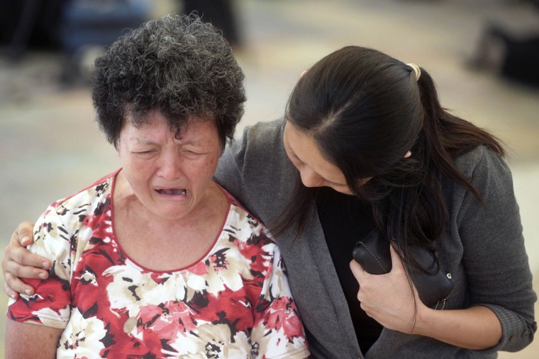 A woman is comforted by a hospital staff member, right, as she cries at Singapore General Hospital where former prime minister Lee Kuan Yew passed away in Singapore, Monday, March 23, 2015. Singapore mourned longtime leader Lee Kuan Yew with raw emotion and a blanket of relentlessly positive coverage on its tightly scripted state television on Monday, mythologizing a man who was as respected as he was feared. (AP Photo/Joseph Nair)