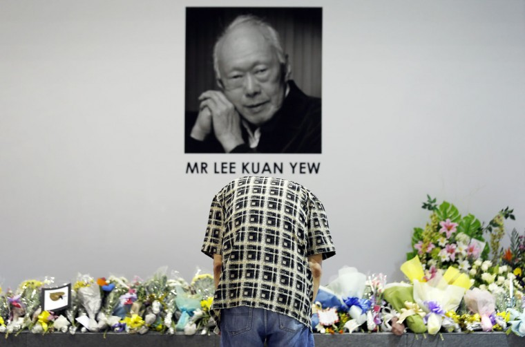 """A man bows to pay his respects to the late Lee Kuan Yew at a community club where members of the public can gather to express their condolences, Monday, March 23, 2015, in Singapore. Singaporeans wept and world leaders paid tribute Monday as the Southeast Asian city-state mourned the death of its founding father Lee Kuan Yew. The government announced that Lee, 91, """"passed away peacefully"""" several hours before dawn at Singapore General Hospital. (AP Photo/Wong Maye-E)"""