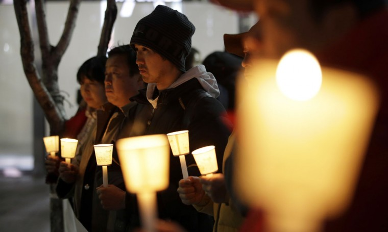 South Koreans hold candles for a quick recovery of injured U.S. Ambassador Mark Lippert in downtown Seoul, South Korea, Thursday, March 5, 2015. Lippert was in stable condition after a man screaming demands for a unified North and South Korea slashed him on the face and wrist with a knife, South Korean police and U.S. officials said. (AP Photo/Lee Jin-man)