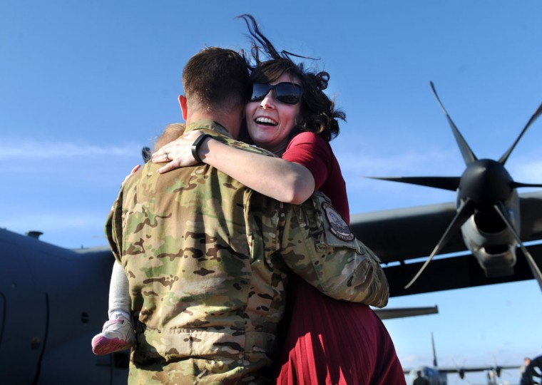 Capt. Josh McVay, front, is reunited with his wife, Bethany and daughter Elise at Dyess Air Force Base, Wednesday, Feb. 4, 2015, in Abilene, Texas. About 35 airmen flew supplies from Senegal to Liberia to aid in the fight against Ebola. (AP Photo/The Abilene Reporter-News, Nellie Doneva)