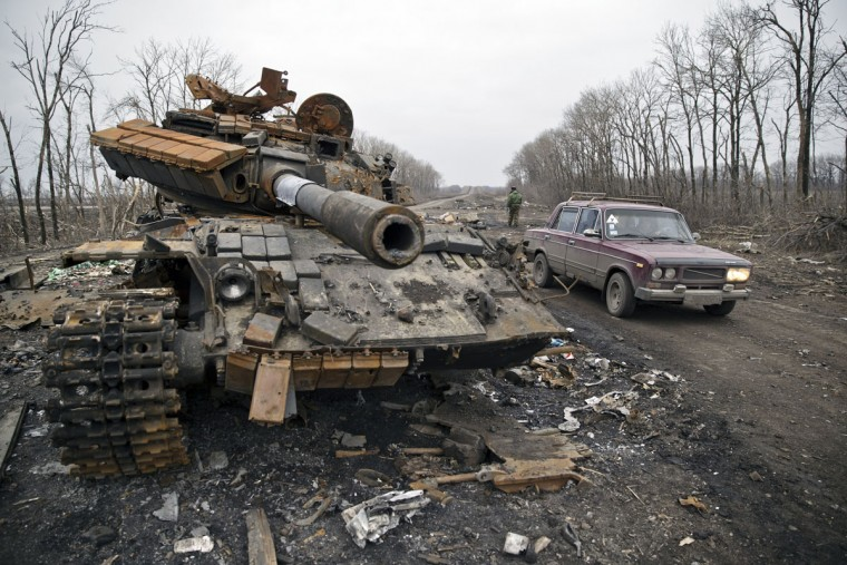 "A car passes a destroyed tank abandoned on the road at a former Ukrainian army checkpoint that was overran last month by Russia-backed separatists during the offensive for Debaltseve, outside the city of Chornukhyne, Ukraine, Monday, March 2, 2015. More than 6,000 people have died in eastern Ukraine since the start of the conflict almost a year ago that has led to a ""merciless devastation of civilian lives and infrastructure,"" the U.N. human rights office said Monday. (AP Photo/Vadim Ghirda)"