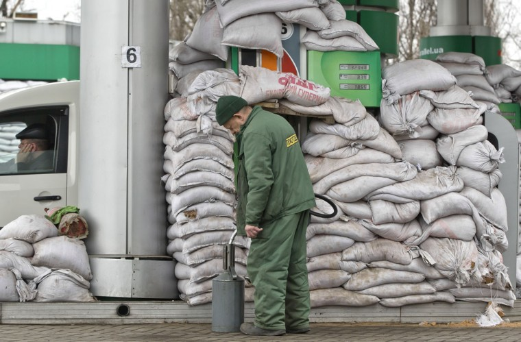 "A man pours gasoline into a canister at a fuel pump covered in sandbags to protect it from possible shelling, in Donetsk, Ukraine, Monday, March 2, 2015. More than 6,000 people have died in eastern Ukraine since the start of the conflict almost a year ago that has led to a ""merciless devastation of civilian lives and infrastructure,"" the U.N. human rights office said Monday. (AP Photo/Vadim Ghirda)"