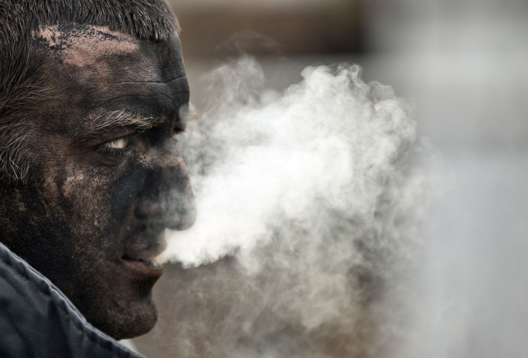 A Ukrainian mining rescuer smokes after taking part in the search for bodies of miners killed in an explosion yesterday before dawn at more than 1,000 metres (3,200 feet) underground at the Zasyadko mine, in Donetsk, Ukraine, Thursday, March 5, 2015. Officials in a separatist rebel-held city in east Ukraine say the death toll from an accidental explosion at a coal mine has risen to 32, while one person still remains unaccounted for. (AP Photo/Vadim Ghirda)