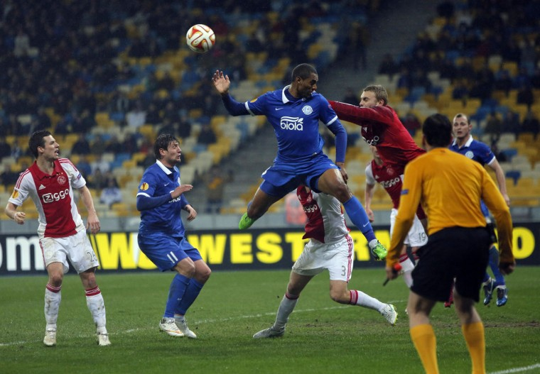 Ajax's Joel Veltman, top right, challenges for the ball against Douglas, center, of Dnipro Dnipropetrovsk during a Europa League, round of 16 first leg soccer match between Dnipro Dnipropetrovsk and Ajax at the Olympiyskiy national stadium in Kiev, Ukraine, Thursday, March 12, 2015. (AP Photo/Sergei Chuzavkov)