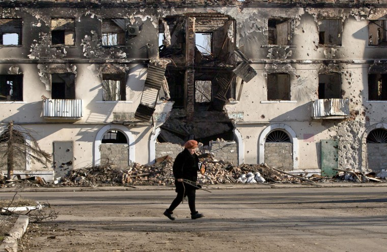 "An elderly woman walks by a destroyed building in Vuhlehirsk, Ukraine, Monday, March 9, 2015. More than 6,000 people have died in eastern Ukraine since the start of the conflict almost a year ago that has led to a ""merciless devastation of civilian lives and infrastructure,"" according to the U.N. human rights office. (AP Photo/Vadim Ghirda)"