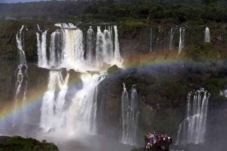 A rainbow forms over tourists visiting Iguazu Falls in Foz do Iguazu, Brazil, on March 15, 2015. The waterfalls, on the border of Argentina and Brazil, are part of the Guarani Aquifer, one of the world's major underground reserves of fresh water. (AP Photo/Jorge Saenz)