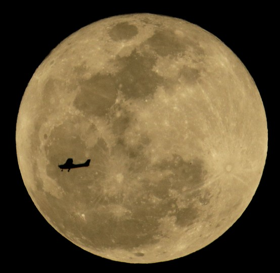 A small plane passes by the moon as it flies over Phoenix, Thursday, March 5, 2015. (AP Photo/Charlie Riedel)