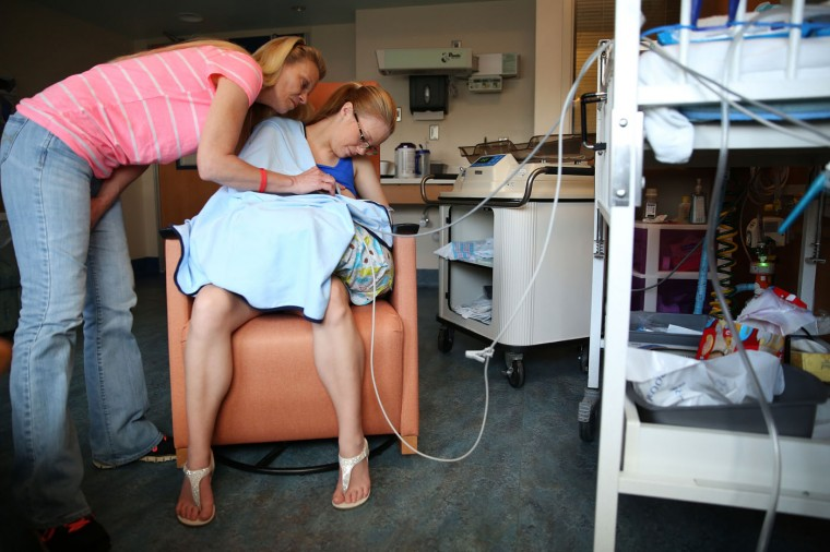 Brandi McGlathery, right, and her mother Norma Mayzes, tends to McGlathery's son Eli at the NICU at USA Children's and Women's Hospital in Mobile, Ala., on March 19, 2015. (AP Photo/AL.com, Sharon Steinmann)