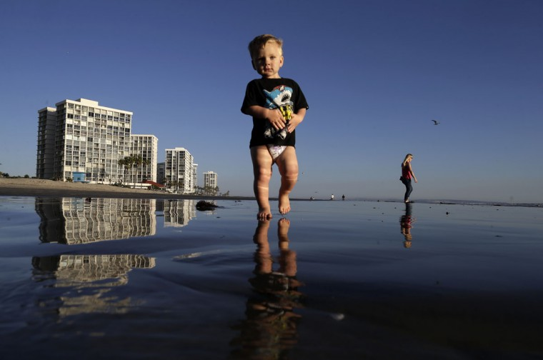 Brodie Harsh, center, walks on the beach as his aunt Dusty Sherriffs, right, passes behind Wednesday, March 4, 2015, in Coronado, Calif. (AP Photo/Gregory Bull)