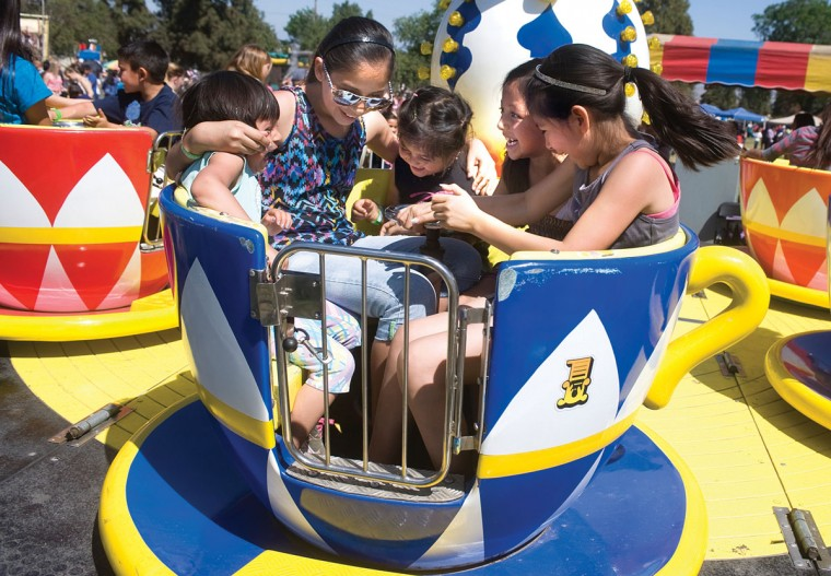 Children enjoy riding tea cups Saturday, March 28, 2015, at Spring Kids Fest at Veterans Park in Porterville, Calif. (AP Photo/The Porterville Recorder, Chieko Hara)